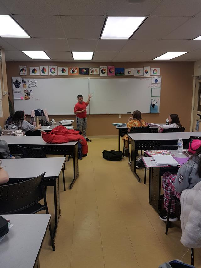 A student stands at the front of a full classroom gesturing to the whiteboard