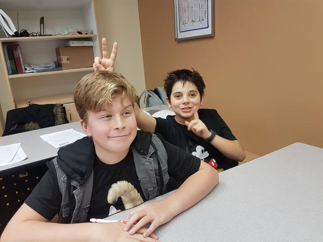 A student sits behind his friends and gives him bunny ears