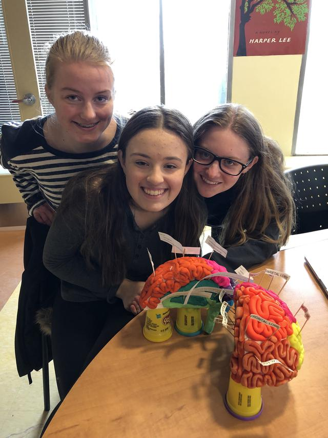 Students pose with their model of a human brain