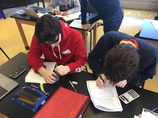 Students write in their notebooks in the science lab