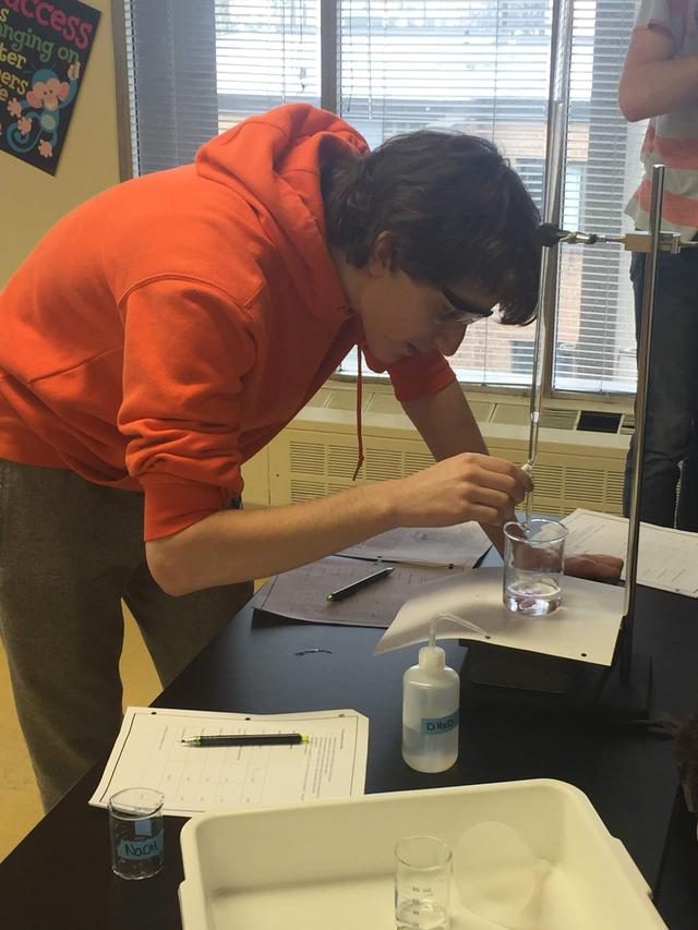 A student performs a science experiment in a lab
