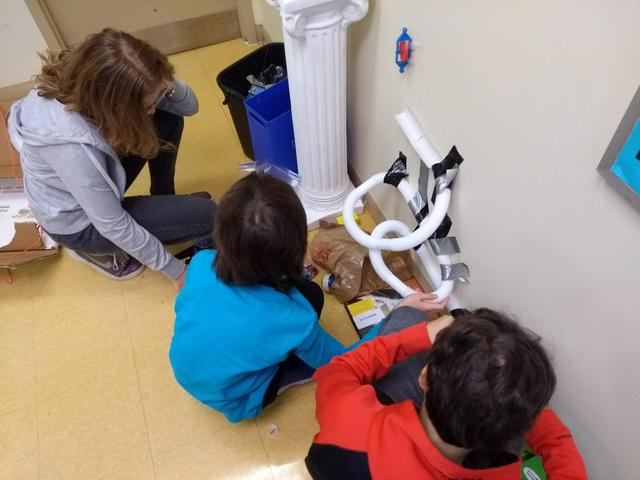 Students tape a pipe to the wall