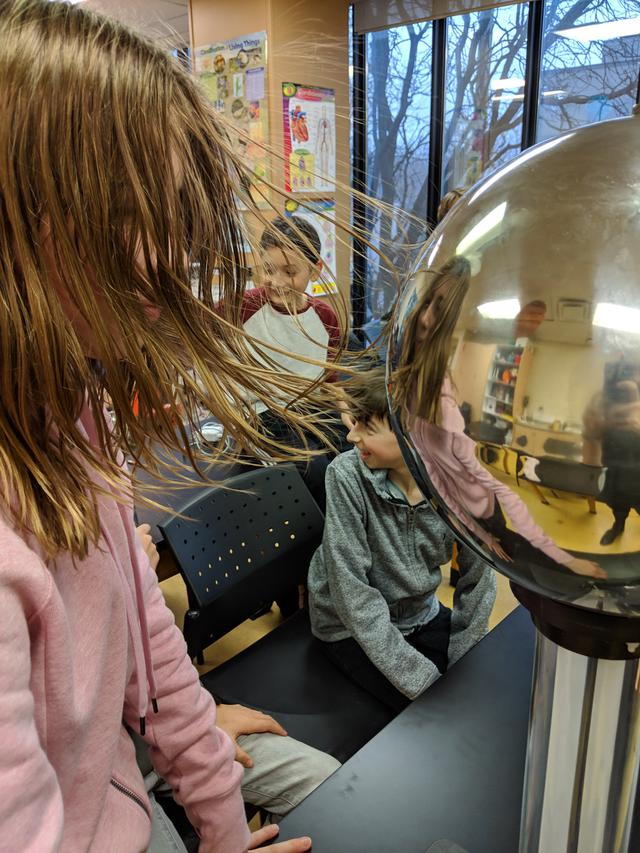 A students hair stands on end due to static electricity