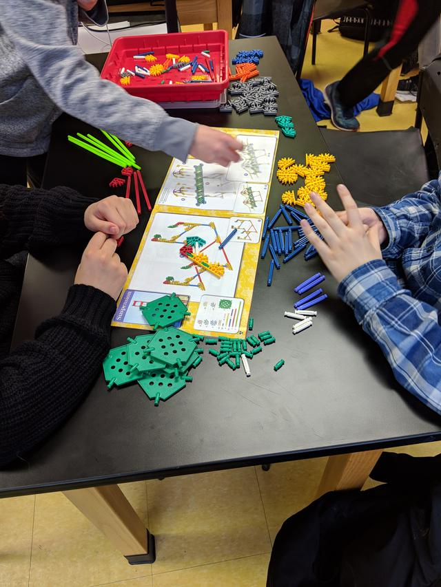 Students look at instructions and build something out of lego
