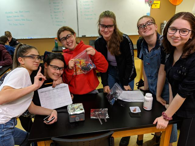 Students smile while wearing safety glasses