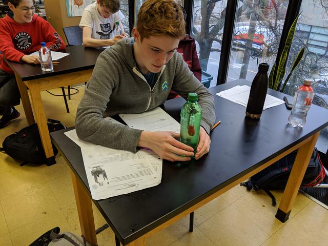 A students sits at a desk staring at a bottle of liquid