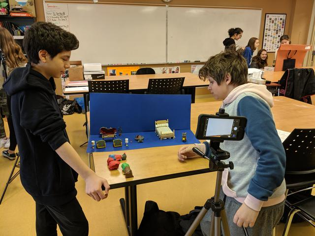 Students take pictures of a scene created from clay