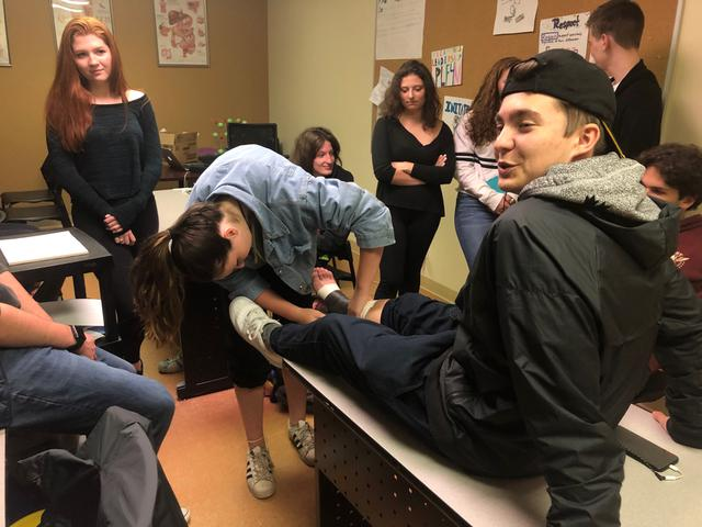 A students wraps tape around another student's leg