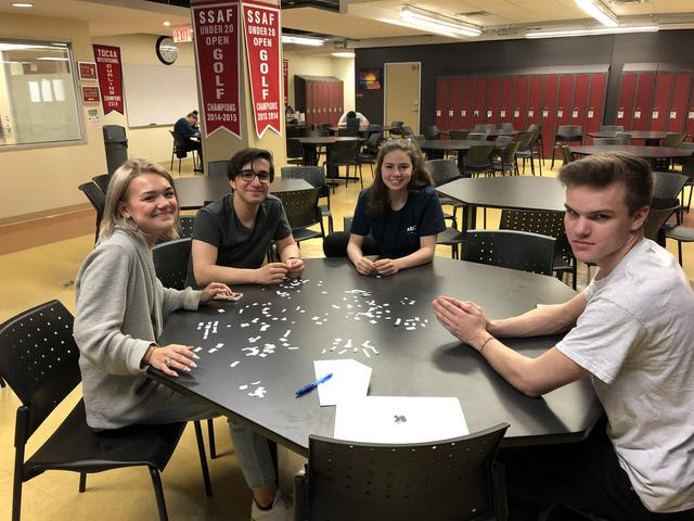 Students sit at a table cutting up paper into small pieces
