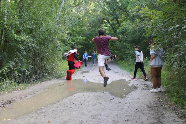 A student leaping over a puddle